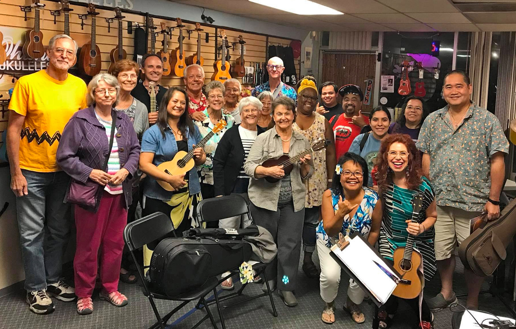 a group of people pose for a picture holding ukuleles