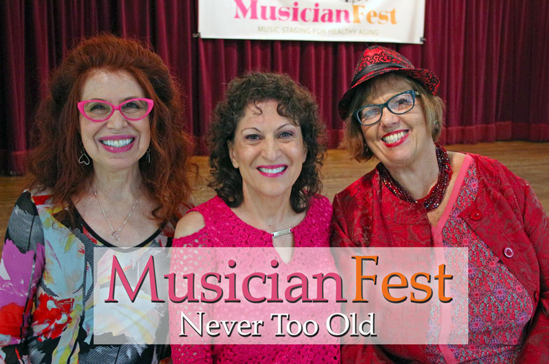 Three mature women smiling. They are dressed in shades of pink and red. A banner with the words Musician Fest appears behind them.