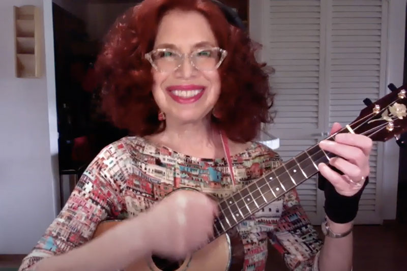 A red haired woman with glasses and a big smile plays a ukulele for the camera. Her hand strums the strings.