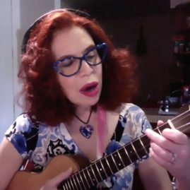 a woman with red hair and glasses plays the ukulele