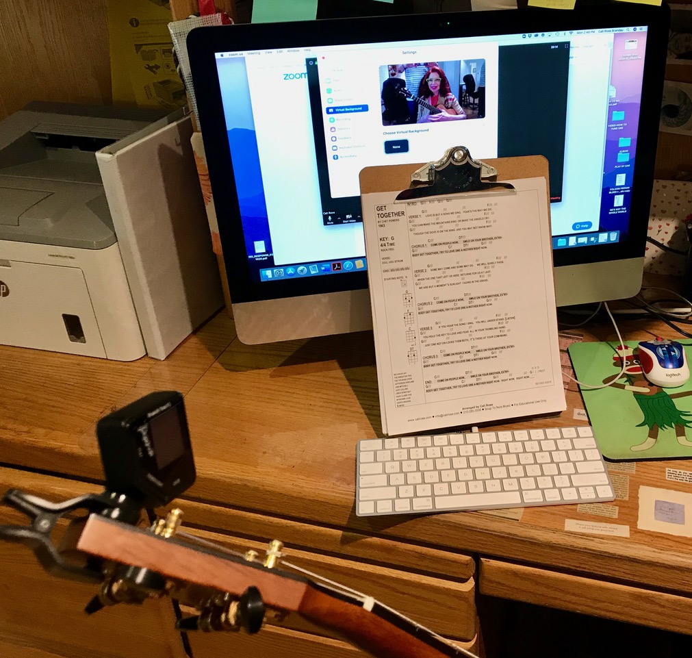 desk with a computer, a clipboard with music