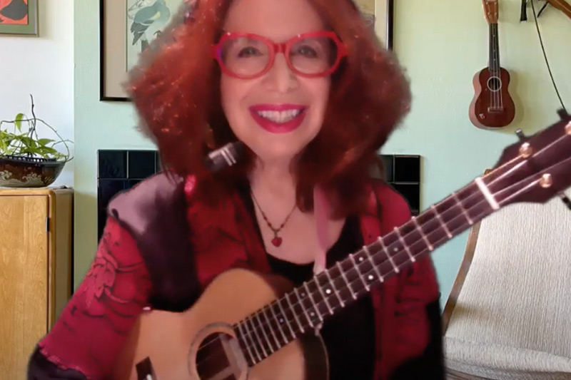 a woman with red hair, glasses, and a ukulele
